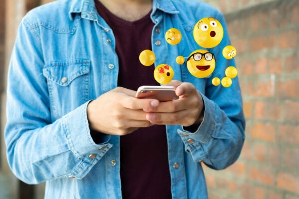 Someone using their phone and a bunch of emoji coming out